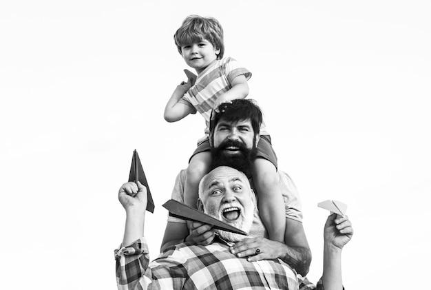 Поколение мужчин. дети играют с простыми бумажными самолетиками в солнечный день. отец дает сыну ездить на спине