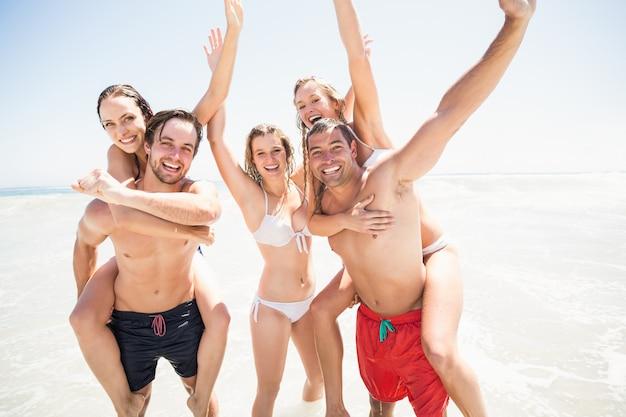Men giving a piggy back to women on the beach