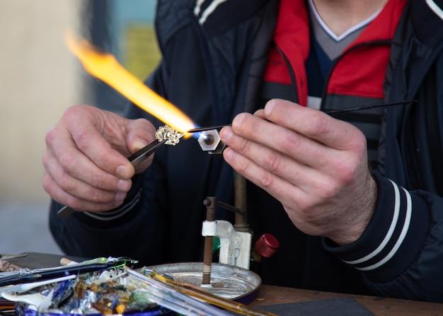 Мужские стеклодувы изготавливают изделия ручной работы под газовой горелкой.