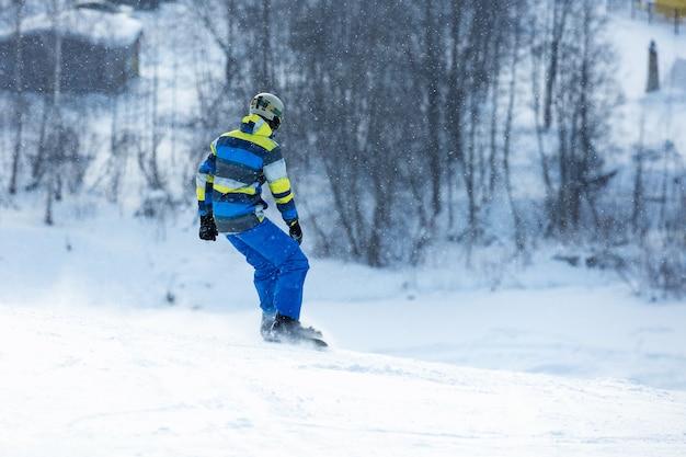 男性は山で雪の上をスキーに行きます。