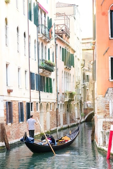 Men gondoliers drive gondolas with tourists in venice in italy.
