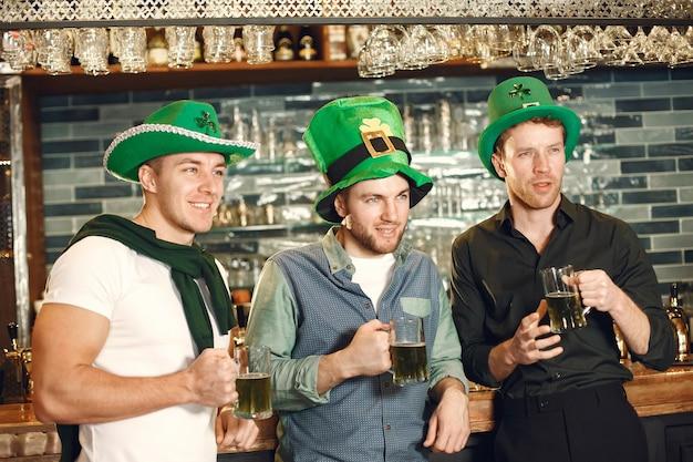 Men in green hats. friends celebrate st. patrick's day. celebration in a pub.