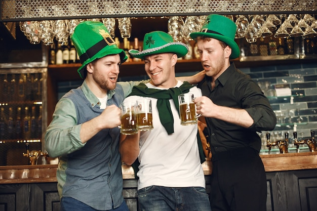 Men in green hats. friends celebrate st. patrick's day. celebration in a pub.
