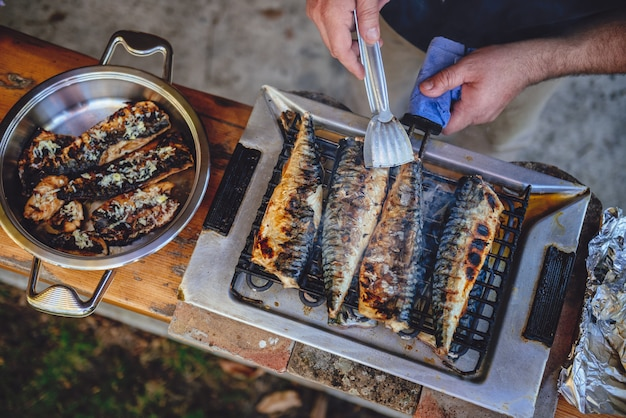 Men grilling fish on electric barbecue