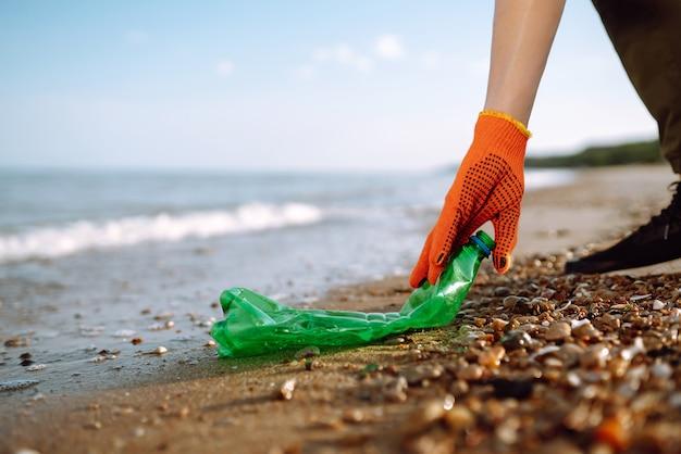 Мужская рука собирает пластиковую бутылку на берегу моря.