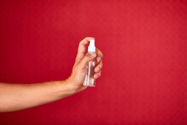 男性の手が赤いスタジオの背景に消毒剤スプレー、コロナウイルス保護装置、消毒消毒剤スプレー、消毒、covid-19パンデミック中の手の消毒保護