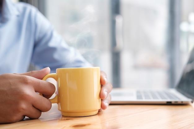 コーヒーやお茶の熱いカップを持っている男性の手。リラックスしてコーヒーブレイクを取りましょう。