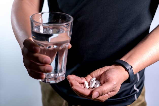 Men hand holding medicine with glass of water medicine recovery concept