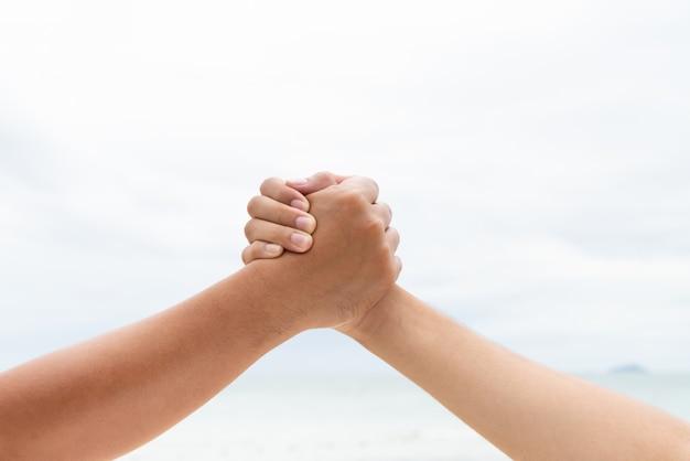 男性の手は一緒に握手します。友情の日の概念。