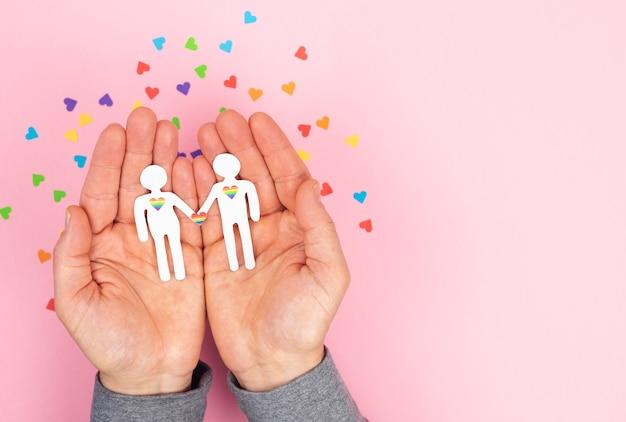 ピンクの背景に紙から切り取ったゲイの男性のカップルを保持している男性の手。バレンタインデー、ゲイプライドデー。 lgbtの概念。
