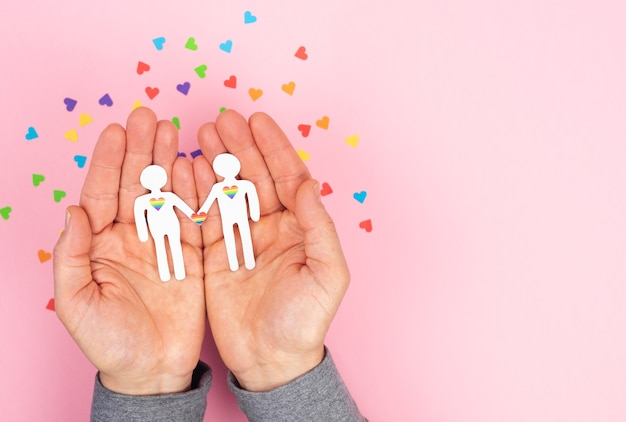 Men hands holding a couple of gay men cut out of paper on a pink background. valentine day, gay pride day. lgbt concept.