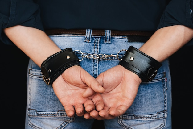 Men hands in leather cuffs behind my back