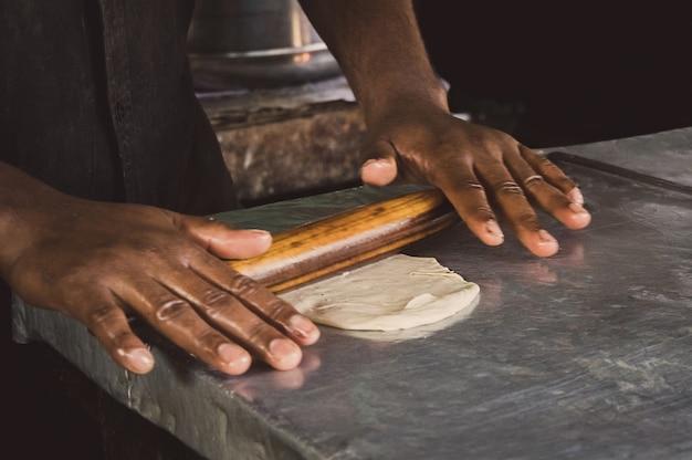 男性の手が生地をクローズアップで広げます。ストリートマーケットで地元のインドのロティを調理するための生地を準備しているアジア人男性。最も人気のあるおいしいスナックを調理するプロセス。屋台の屋台。