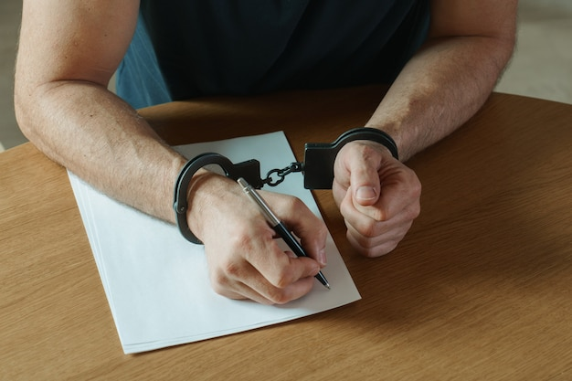 Men hands with handcuffs fill the police record, confession. on top of the police investigative