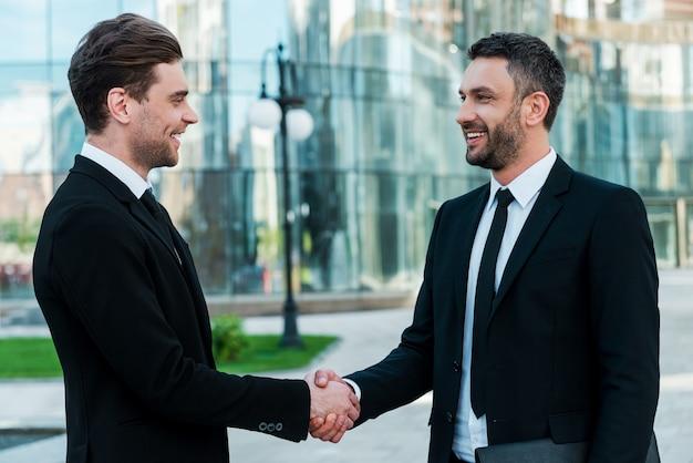 Мужчины рукопожатия. два уверенных в себе молодых бизнесмена пожимают друг другу руки и улыбаются, стоя на открытом воздухе