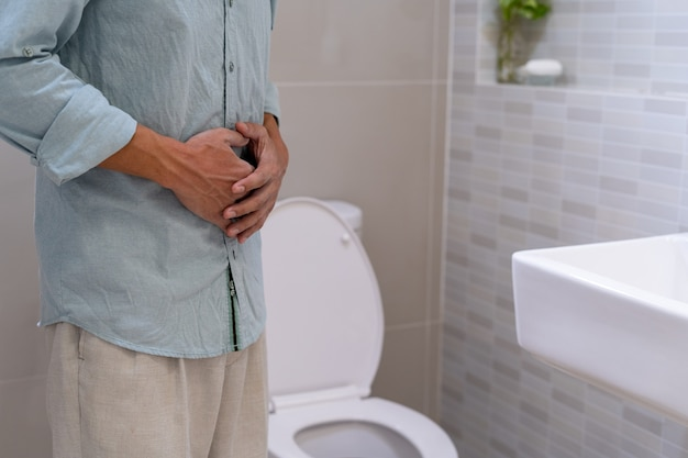 Men have abdominal pain, holding their hands on their abdomen, torturing the face of the toilet in the toilet.