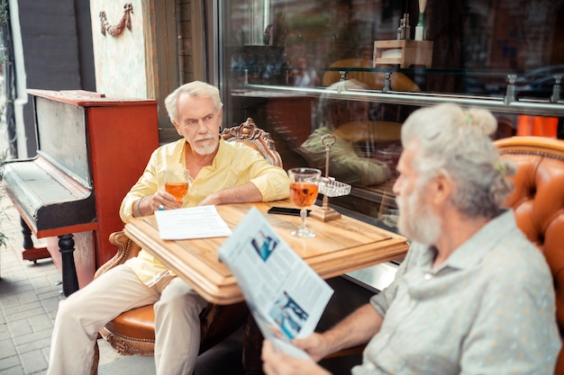 Men having conversation. grey-haired retired men having conversation sitting outside the cafeteria