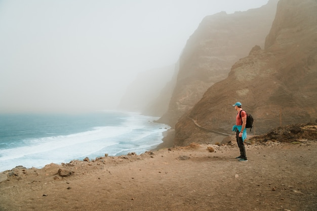 Men hiker with backpack on the scenic coastal road. the route leads along huge volcanic rock cliffs above roaring ocean and joins the towns of cruzinha and ponta do sol. santo antao. cape verde.