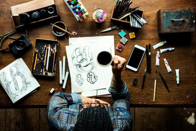 Мужчины хипстер, держащий кофе и иллюстрации на столе