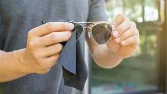 男性はサングラスを握って清潔にする。
