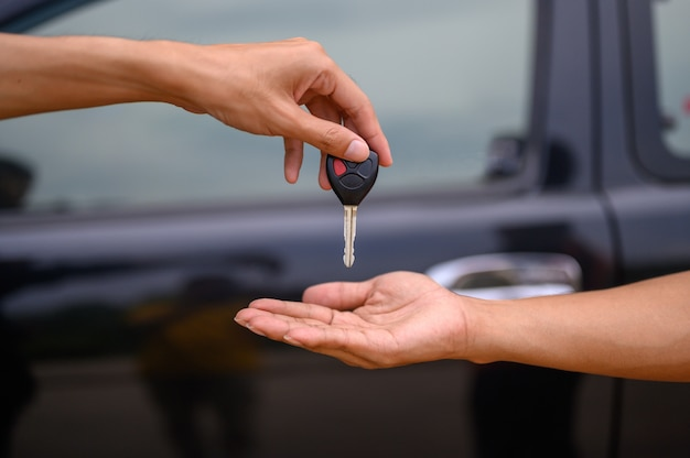 Men hold the car keys to submit to the staff to pick up the car.