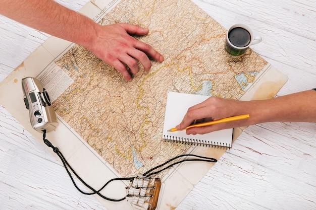 男性はコーヒー、cmaera、ノートブックで地図上に手を置く
