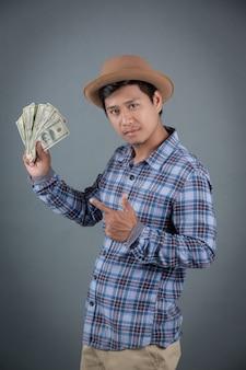 회색 배경에 달러 은행을 들고 남자.