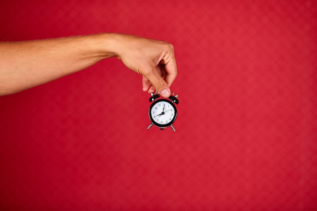 Men holding black alarm clock in one hand on red studio background, copy space
