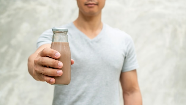 Men holding a bottle of chocolate milk on gray background.
