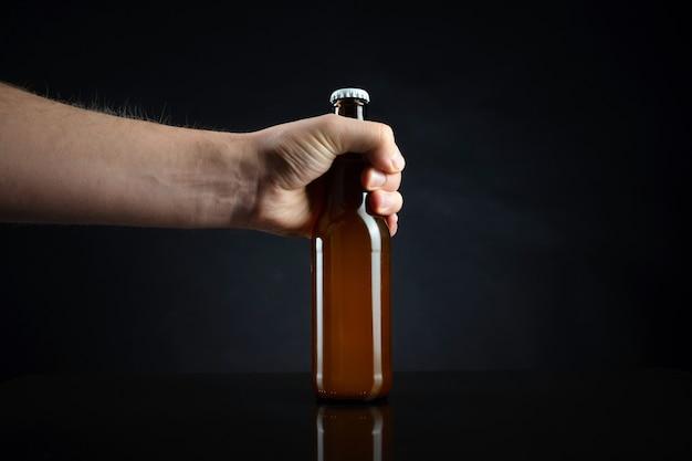 冷たい未開封のビールのボトルを持っている男性。