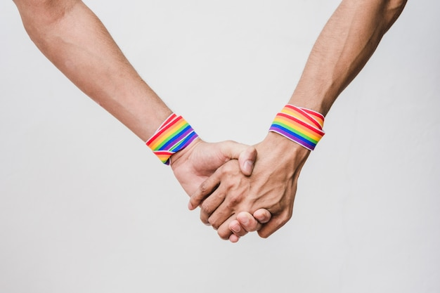 Men holding hands with bands in lgbt colors