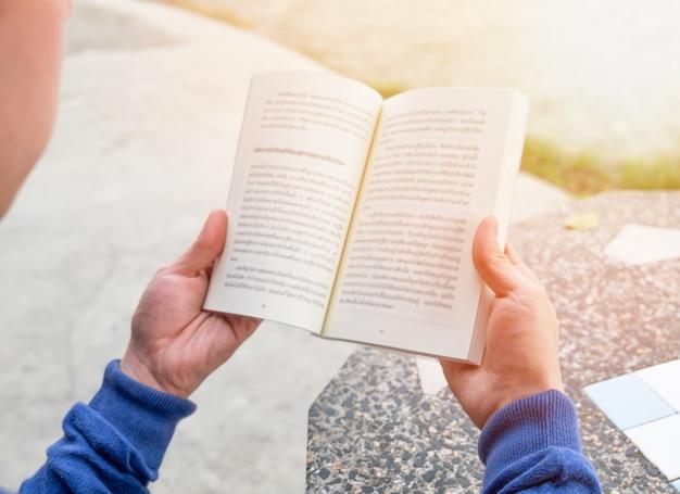 Мужчины, держащие книгу для чтения на столе, эффект солнечного света