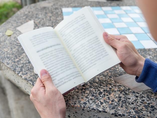 Мужчин, занимающих книгу для чтения на столе