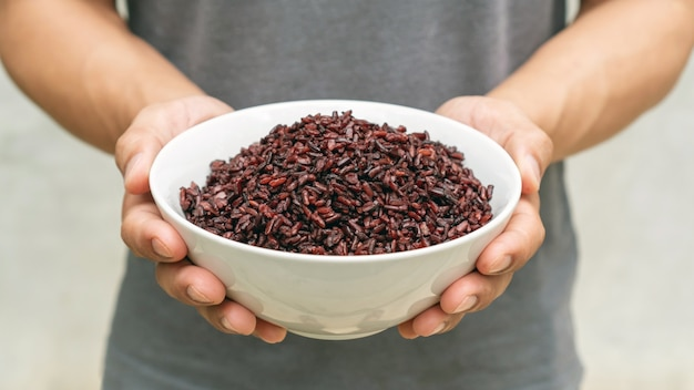 Men holding a riceberry in a white bowl.