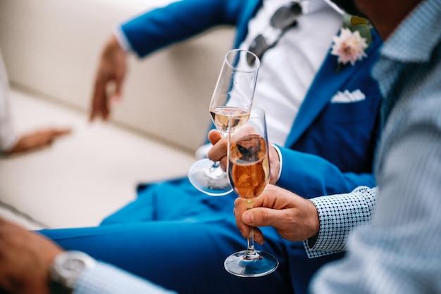 파란 양복에 남자는 소파에 앉아 그들의 안경을 clang