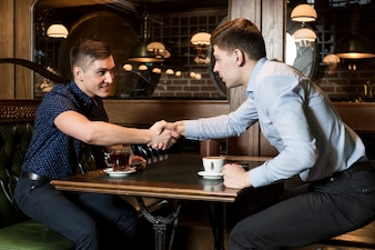 Men in cafe shaking hands