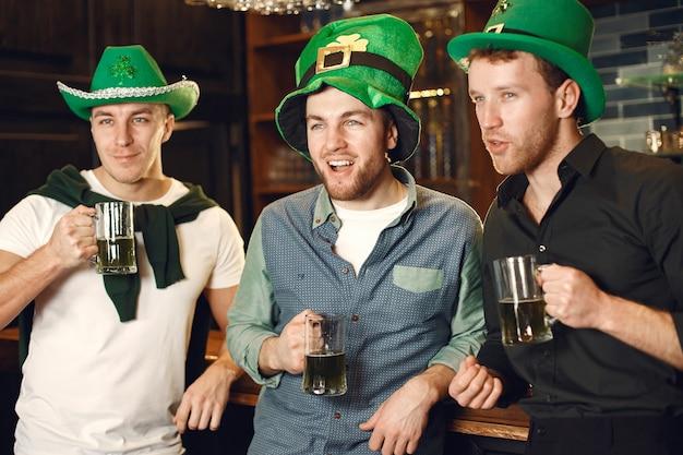 Мужчины в зеленых шляпах. друзья отмечают день святого патрика. праздник в пабе.