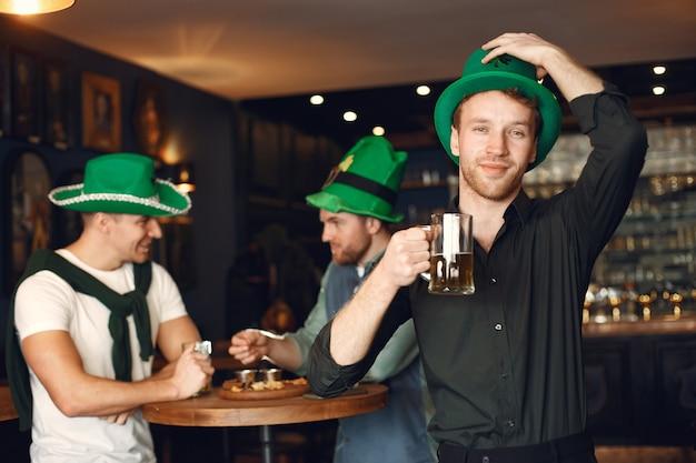 녹색 모자에있는 남자. 친구들은 성 패트릭의 날을 축하합니다. 술집에서 축하.