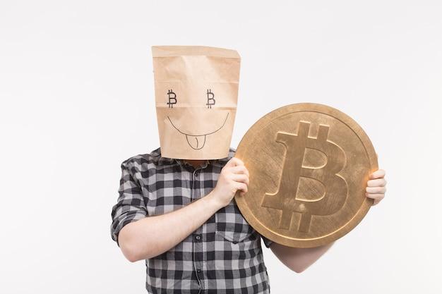 Мужчины в счастливой маске бумажного мешка с биткойном на руках.