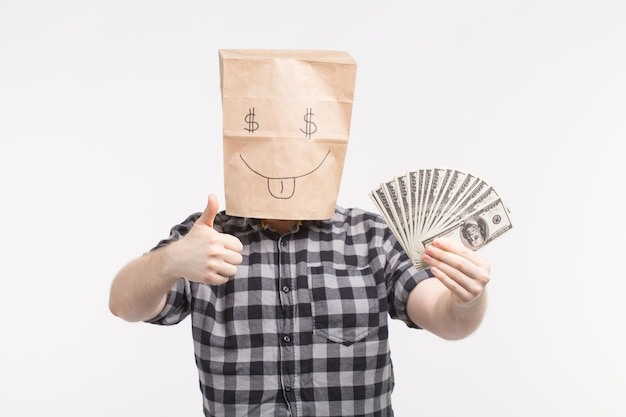 白い背景に親指を示す紙幣と幸せな紙袋マスクの男性