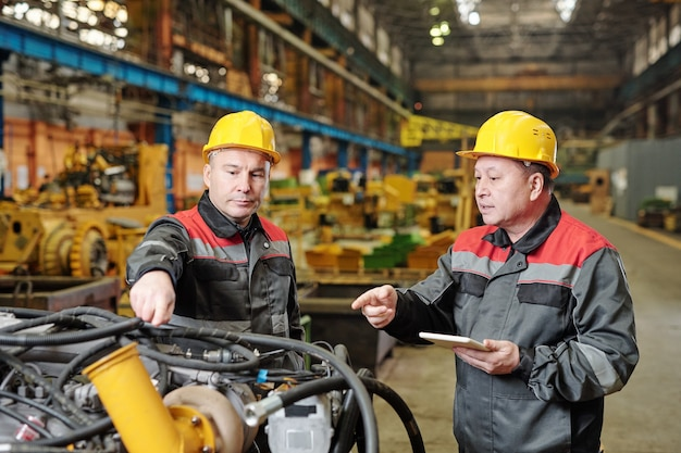Мужчины в касках работают на машине