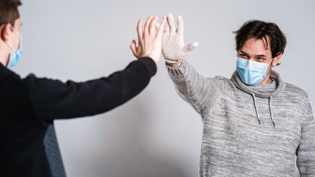 マスクと手袋をした男性が社会的距離を決定するために手を伸ばします