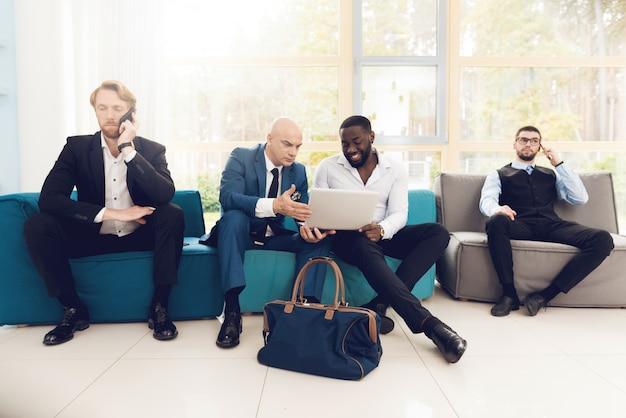 정장을 입은 남자들이 공항 강당에 앉아 있습니다.