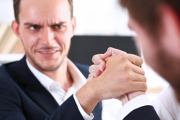 정장 입은 남자들이 레슬링에 손을 잡는다.
