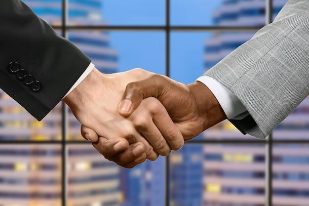 スーツを着た男性が握手します。夕方の背景にビジネス握手。一緒に勝ちます。平等と寛容。