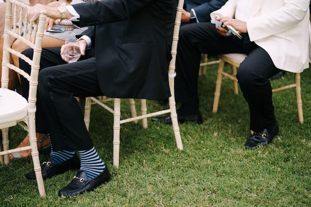 スーツを着た男性は芝生の椅子に座っています