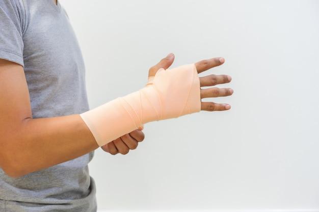 탄력 붕대를 사용하여 힘줄 염증으로 부상당한 남성. 부상을 줄이고 부기를 줄입니다. 의료 및 건강 관리 개념