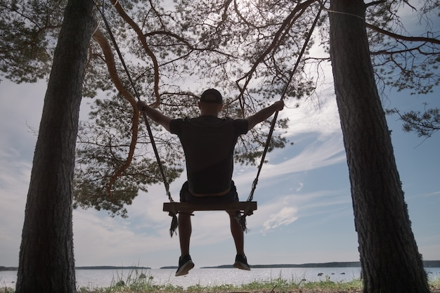 A men is swinging on a swing on the shore of the lake. the swing is suspended from trees. back view