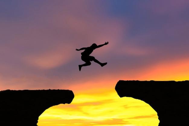 Men jump cliff sun light over silhouette concept