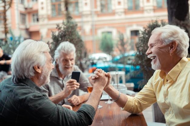 笑っている男性。パブの外に座って腕相撲をしながら笑っている陽気な白髪の男性